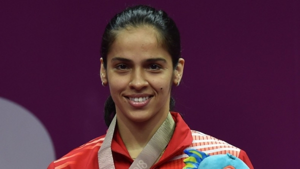Saina Nehwal stands at the podium after winning the gold medal in the singles competition.