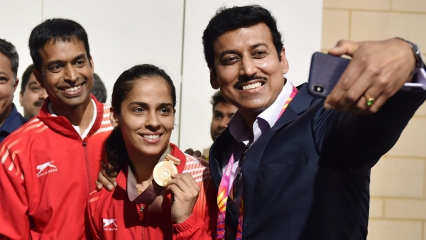 P Gopichand (left) poses with Gold Medalist Saina Nehwal (centre) and Sports Minister Rajyavardhan Rathore (left) after Saina Nehwal's gold medal win against teammate PV Sindhu.