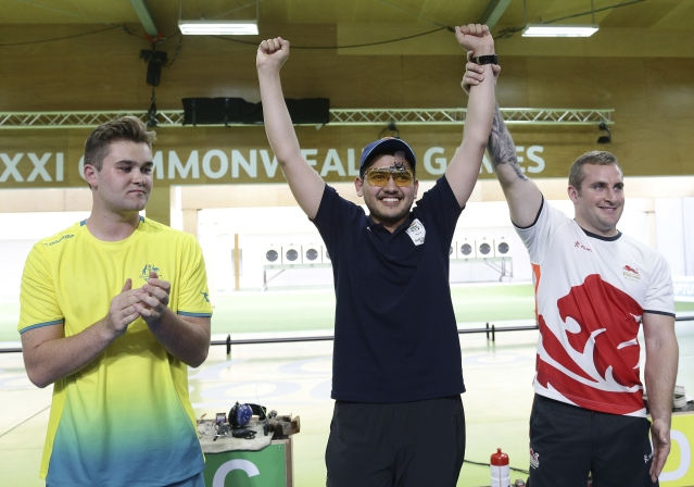 Sergei Evglevski of Australia, left, silver medal, Anish of India, center, gold medal, and Sam Gowin of England, right, bronze medal, during the men's 25m Rapid Fire Pistol final at the Belmont Shooting Centre during the 2018 Commonwealth Games