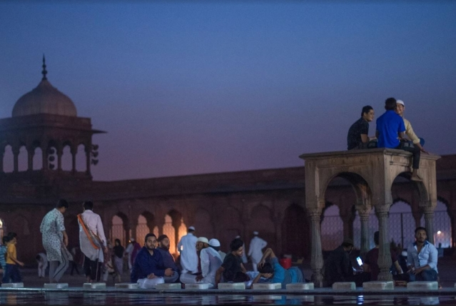 People rest around the pool after <i>'Fajr Namaaz'.</i>
