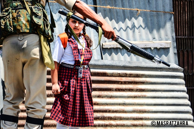 A girl in uniform looks at the pellet gun during a curfew in Old Srinagar on 28 July 2017.