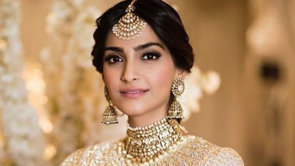Sonam Kapoor makes a stunning bride in an ivory and gold lehenga by Abu Jani Sandeep Khosla.