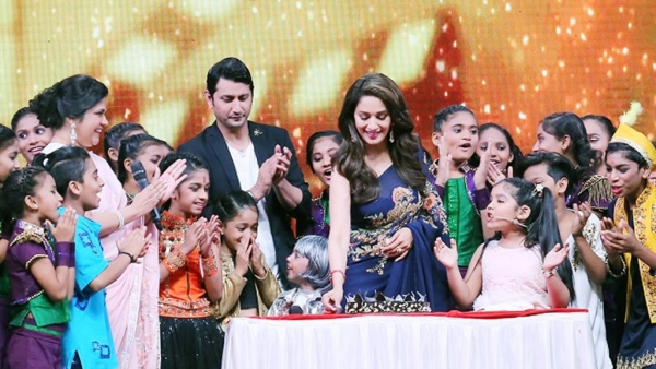 Madhuri Dixit cuts a birthday cake with Renuka Shahane (left) and the participants of <em>DID Lil Masters.</em>