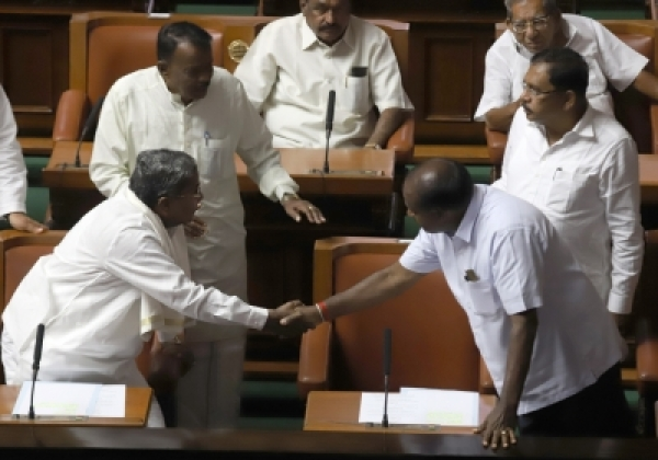 Bengaluru: Congress leader Siddaramaiah greets Karnataka Chief Minister H.D.Kumaraswamy at the state assembly in Bengaluru on May 25, 2018. (Photo: IANS)