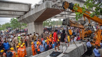 At least 18 people were killed and several trapped under the rubble after a portion of an under-construction flyover collapsed in Varanasi.