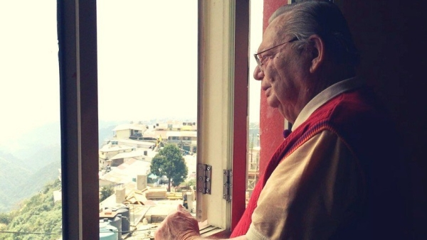 Ruskin Bond stands, watching the mountains outside his home in the hills.