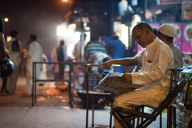 A man reads a newspaper outside one of the many eateries that are open well into the wee hours.