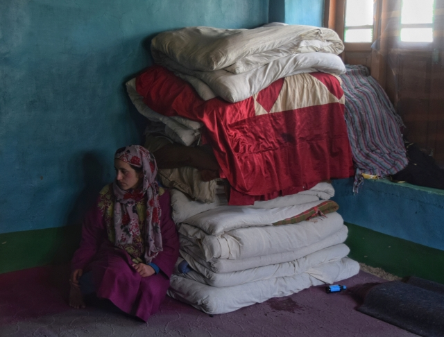 The elder sister of Amir Hameed Lone sitting by his bedding inside his room.