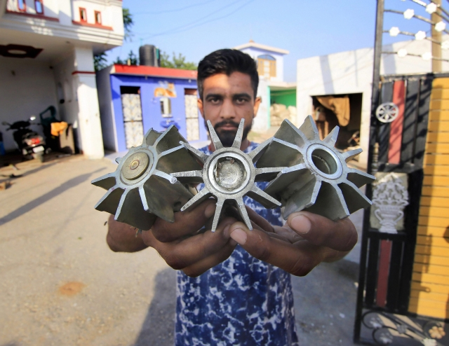 A villager shows tails of mortar shells, claimed to be fired from the Pakistani side, along the International Border at Gopper Basti in Jammu.