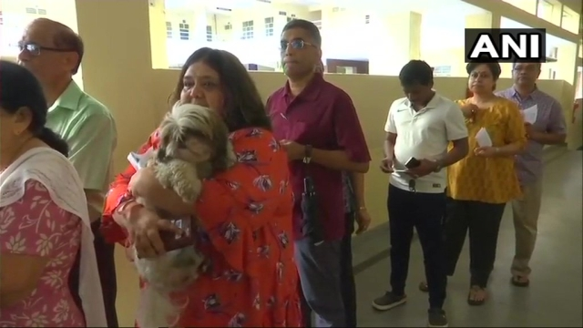 A woman waits in queue at polling booth number 172 in BTM constituency, with her dog in tow.