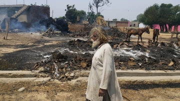 An Indian man inspects the damage after  was gutted by firing allegedly from the Pakistan side of the border.