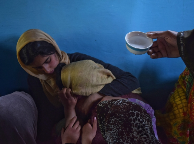 Relatives consoling Amir Hameed Lone's younger sister and offering her water as she mourns his death.