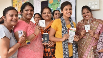 Voters show their voting ID as they cast their vote for Karnataka Assembly elections in Hubballi on Saturday.