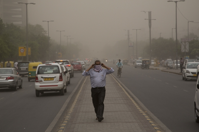 A man wraps a scarf around his nose as a dust storm envelops the city in New Delhi, Wednesday, May 2.