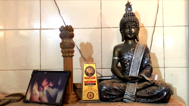 The picture of Haribabu's youngest son on a table along the Buddha idol. In the middle is an award given to his granddaughter by the Buddhist Society of India for performing well in her studies.