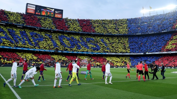 The Real Madrid and Barcelona players enter the field as the fans are ready with their message at Camp Nou.