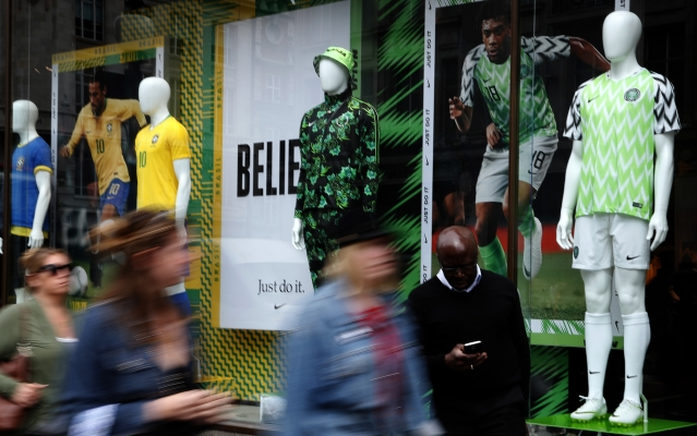People walk by Nigerian and Brazil national soccer team jerseys which are on display at a shop in London.