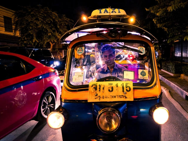 A tuk tuk waits for the traffic signal to turn green.