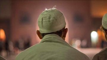 A man sits at Jama Masjid.