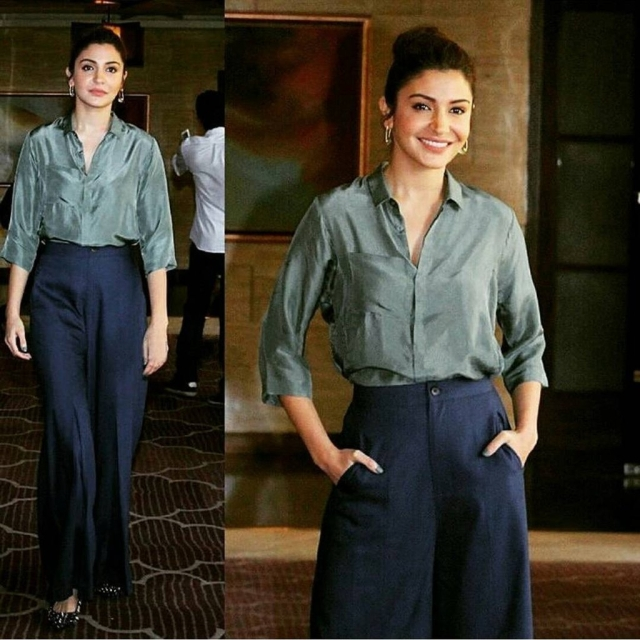 Anushka Sharma paired a military green silk shirt with black wide legged trousers.