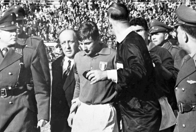 In this file photo from 2 June 1962, Italian forward Giorgio Ferrini, centre, is sent off by British referee Ken Aston, back to camera, after an incident during the first half of the World Cup match between Italy and Chile in Santiago, Chile. Ferrini refused to leave the field after being ordered off by the referee and was removed by police officers.