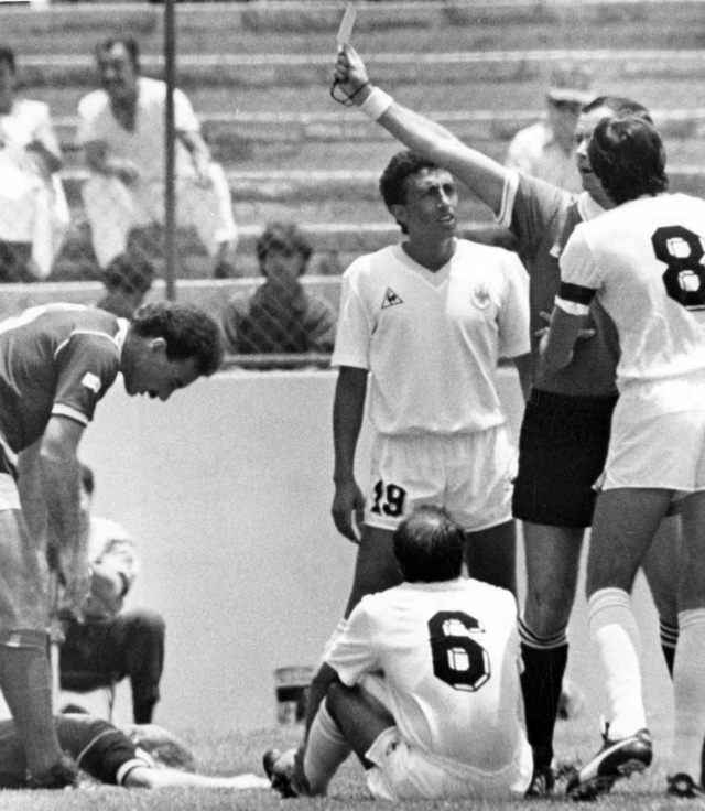 In this 13 June 1986 filer, French referee Joel Quiniou, rear right, shows the red card to Uruguayan player Jose Batista, No 6, for a bad tackle on Scotland's Gordon Strachan, on the floor left, just one minute after the start of the Football World Cup match between Scotland and Uruguay in Mexico City, Mexico. The first red card of the Russia 2018 World Cup tournament has been awarded against Colombia midfielder Carlos Sanchez for handling a goal-bound shot in the area in the third minute against Japan. Shinji Kagawa slotted the resultant penalty to give Japan an early 1-0 lead in the World Cup Group H game.