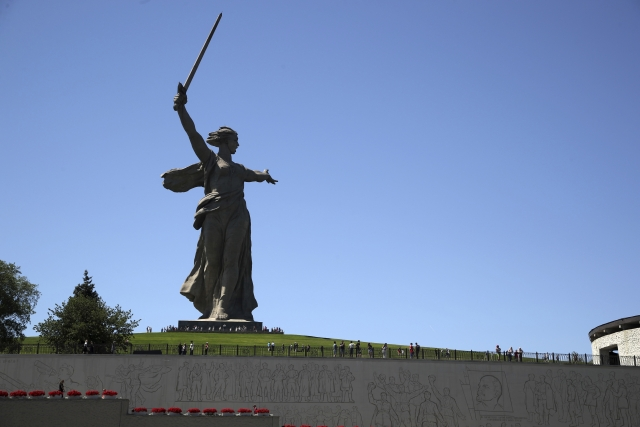 In this Sunday, June 17, 2018 photo, tourists visit the Motherland Calls monument which commemorates the victims of the Battle of Stalingrad, in which the Red Army turned back Nazi Germany's army in Volgograd, Russia.