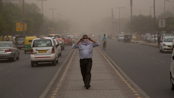 A man wraps a scarf around his nose as a dust storm envelops the city in New Delhi, on Wednesday.