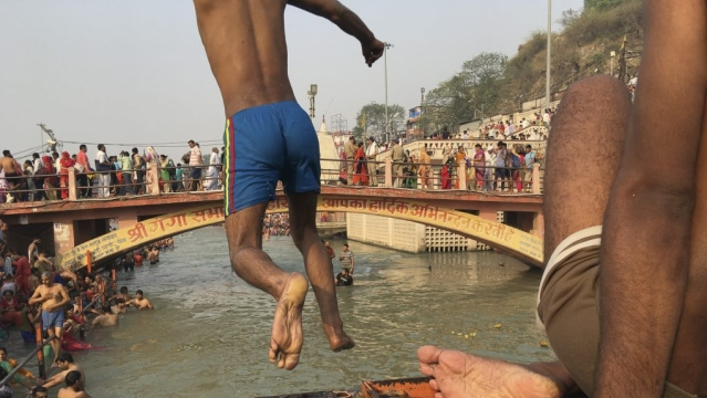 Young men jumping into the fast flowing waters at Har Ki Pauri, each trying to jump higher, and more times, than the rest.