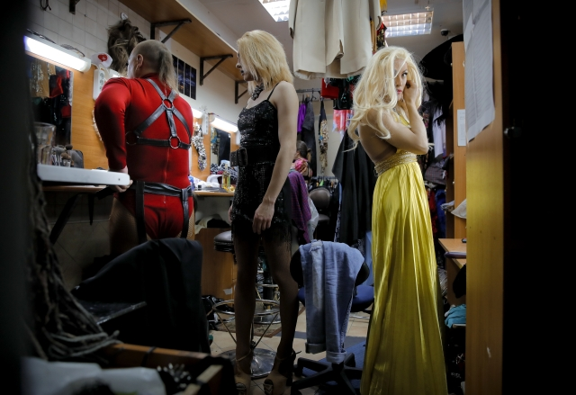 Andrei, who uses the stage name Star Vasha, right, Dmitry, who performs under the stage name Africa, center, and Sergey, or artistic name Bomba (The Bomb), prepare before performing at a Gay club during the 2018 soccer World Cup in Yekaterinburg, Russia.