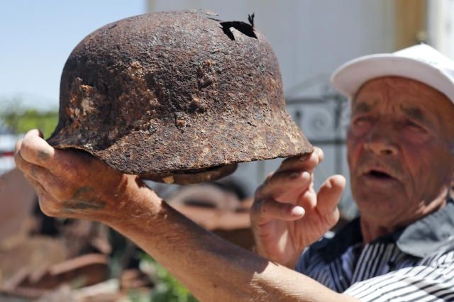 72 year old Vitaly Danilkin holds up memorabilia and remains of battles that took place near Stalingrad, in Rossoshka, Russia.