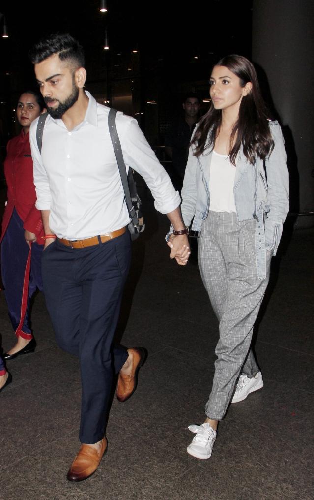 Virat Kohli and Anushka Sharma walking hand in hand outside the airport.