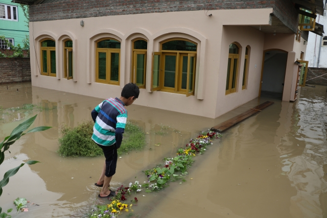 A child navigates the submerged pathway  to his house.
