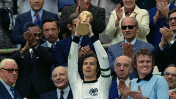 Franz Beckenbauer lifts the FIFA World Cup trophy as captain of the winning West Germany team in 1974.