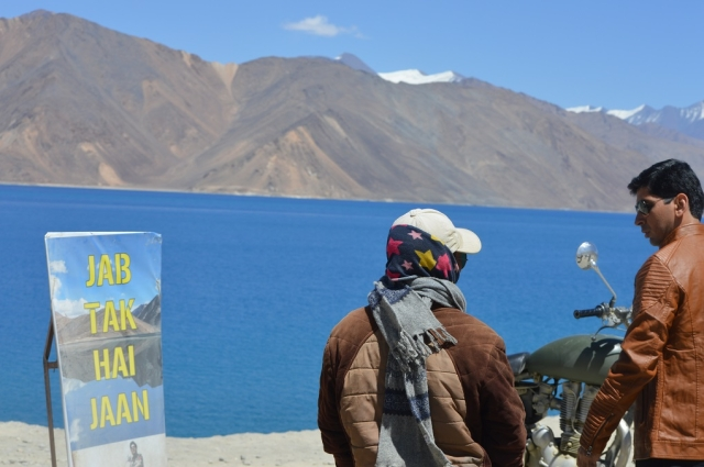 Two tourists near a poster of the movie 'Jab Tak Hai Jaan'.