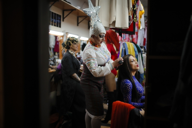 Sergey, who uses the stage name Bomba (the bomb) combs the hair of Andrei, or Star Vasha, right, as they get ready to perform at a Gay club during the 2018 soccer World Cup in Yekaterinburg, Russia.