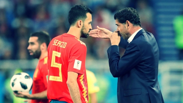 Spain head coach Fernando Hierro, right, speaks to Sergio Busquets during a World Cup match.