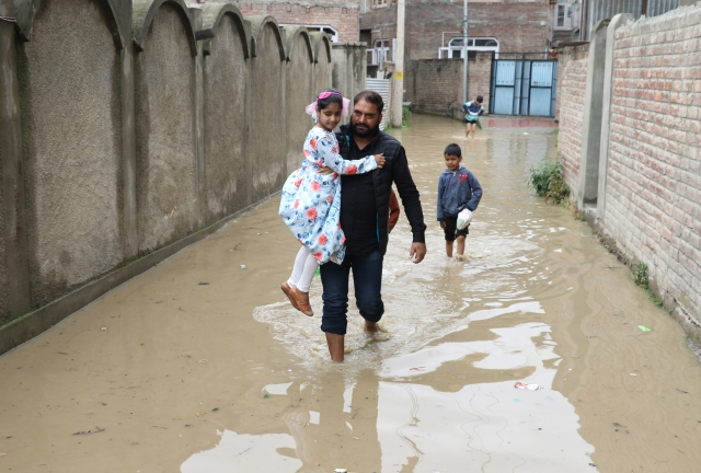 Citizens wade through Srinagar's water-logged streets.