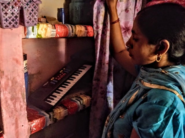 Abhishek's mother showing his piano, which was kept behind curtains as there was no one to play with it in his absence.