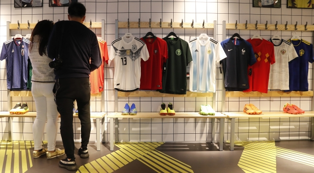 Customers look at different national soccer team jerseys that are on display at a shop in London. With just days to go before the FIFA World Cup, some winners and losers have emerged among the often wild and wacky team jerseys.