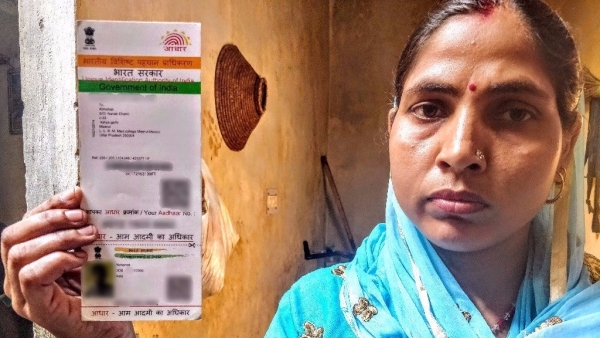 Abhishek's mother Sundari holds up her son's Aadhaar card with the year of birth as 2006.