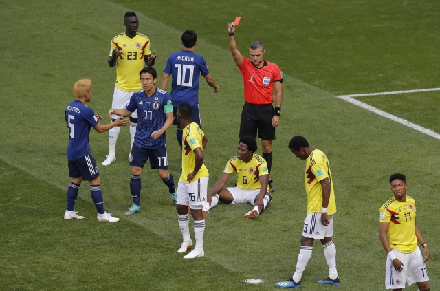Referee Damir Skomina from Slovenia shows a red card to Colombia's Carlos Sanchez, on the ground, during the group H match between Colombia and Japan at the 2018 football World Cup.