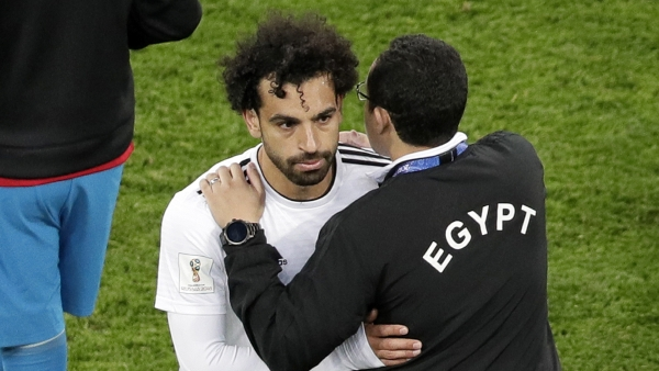 A Egypt's team official comforts Egypt's Mohamed Salah after the group A match between Russia and Egypt at the 2018 soccer World Cup in the St. Petersburg stadium in St. Petersburg, Russia, Tuesday, June 19, 2018.