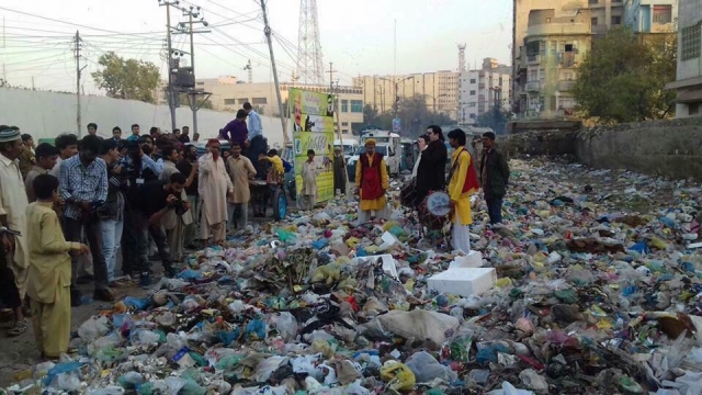 Motiwala addresses people while standing on a pile of garbage.