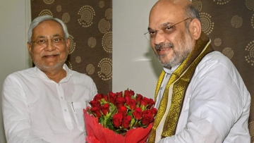 Bihar CM Nitish Kumar and BJP President Amit Shah exchange greetings at the state guest house, in Patna on Thursday, July 12.