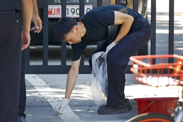 A crime scene investigator collects fragments from the spot of the blast outside the US embassy in Beijing