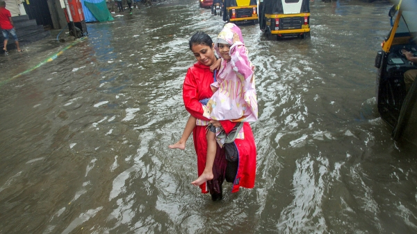 A mother carries her child in a water-logged street of Mumbai