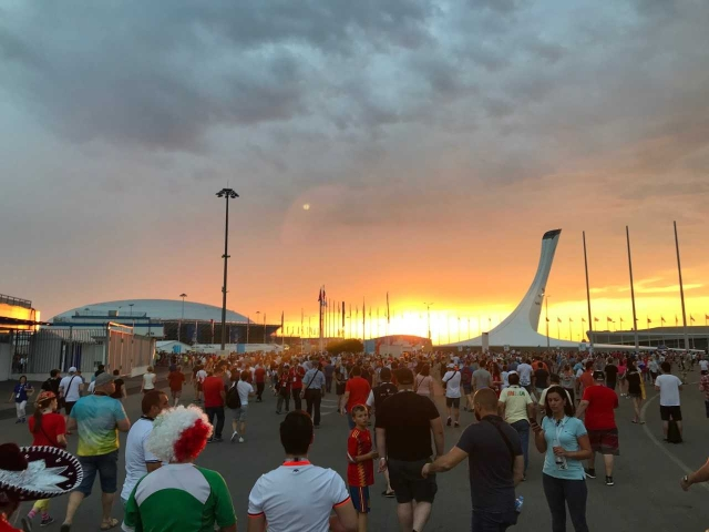 The fiery glow of the setting sun behind the Olympic torch next to the Fisht Stadium welcoming the Portugal and Spain fans.