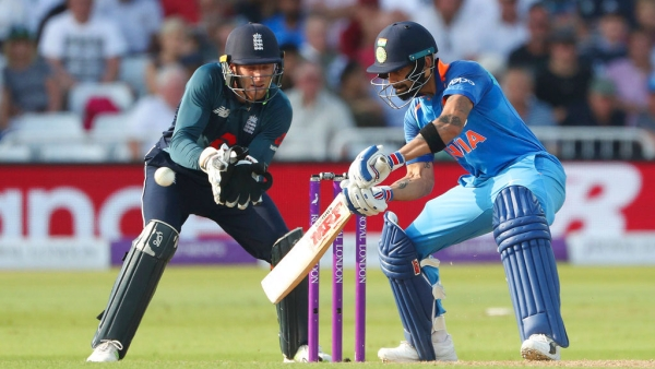 Virat Kohli plays a shot as wicket-keeper Jos Buttler looks on.