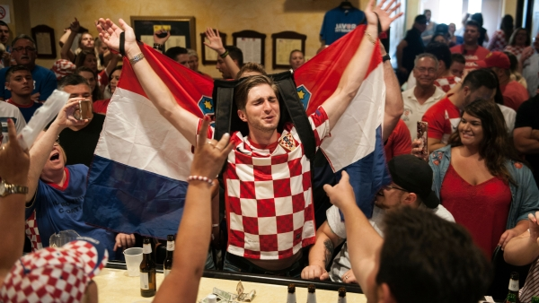 Marko Luketich Kochis, center, 26, of Cokeburg, raises the Croatian flag as he celebrates his team being in the World Cup final alongside other people of Croatian decent gathered to watch the game on Sunday, July 15, 2018.